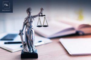 waage der justitia bücher auf dem tisch